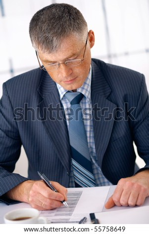Elder business manager working on some document in the office. - stock photo