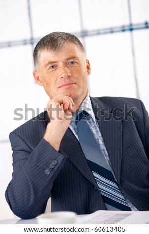 Elder businessman smiling and sitting at his office - stock photo