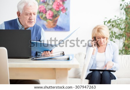 Elder businesspeople checking important docuemnts of their company - stock photo
