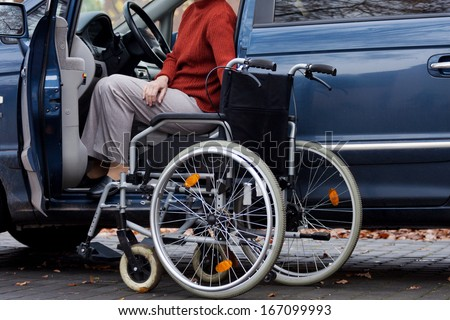 Elder disabled person driving a car - stock photo