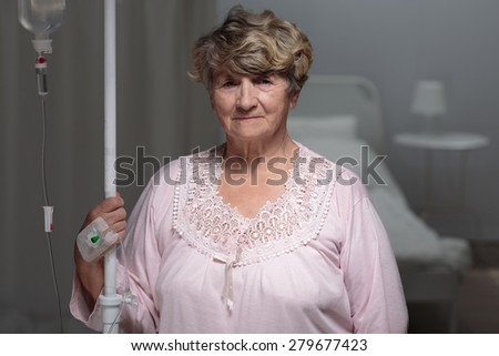 Elder female patient walking with drip stand - stock photo