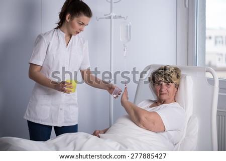 Elder patient refusing to take a medicine - stock photo