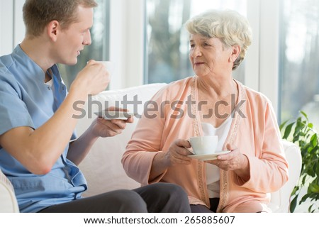 Elder woman and male nurse drinking coffee - stock photo
