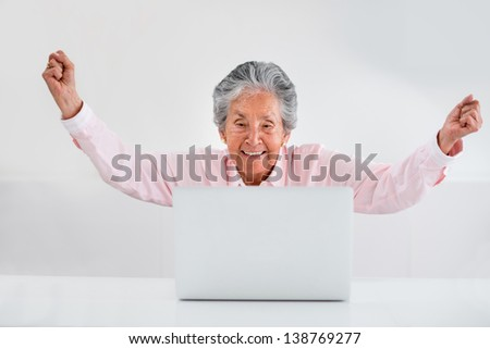 Elder woman celebrating her online success with arms up - stock photo