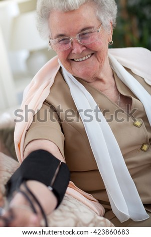 Elder woman getting her blood pressure checked - stock photo