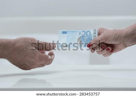 Elder woman handing an euro banknote to elder man - stock photo