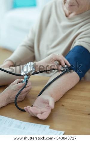 Elder woman having measured blood pressure by cardiologist - stock photo