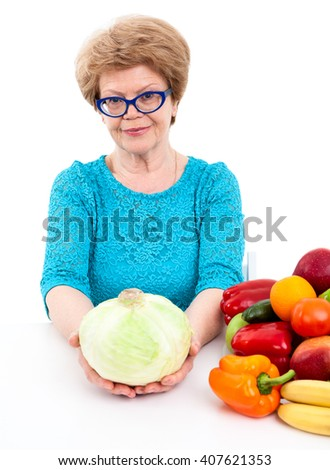 Elder woman holding cabbage in hands, sitting with fresh fruit and vegetables on table, isolated on white background - stock photo