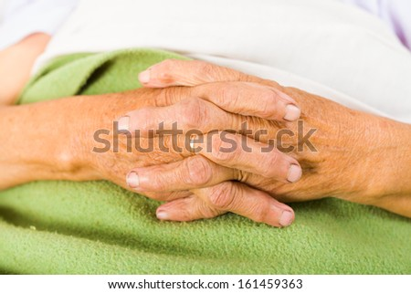 Elder woman in bed saying her daily prayers. - stock photo