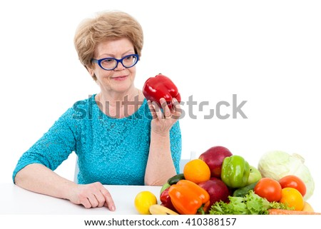Elder woman looking at red sweet pepper in hand, sitting with fresh fruit and vegetables on table, isolated on white background - stock photo