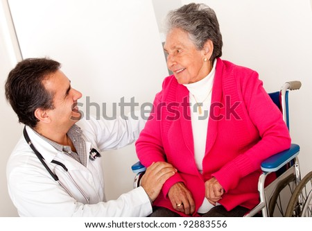 Elder woman sitting in a wheelchair at the hospital talking to the doctor - stock photo