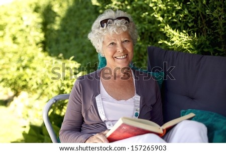 Elder woman sitting on a chair in backyard garden holding a book and looking at camera smiling - stock photo