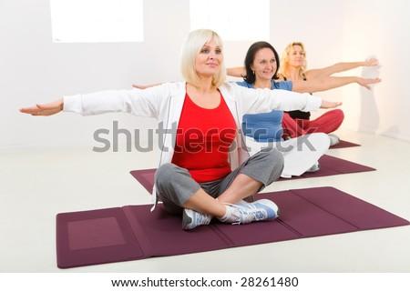 Elder women sitting cross-legged on mat and doing exercices. - stock photo