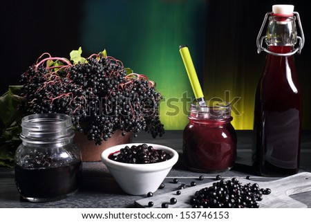 elderberry jam and berries syrup gray table green background - stock photo