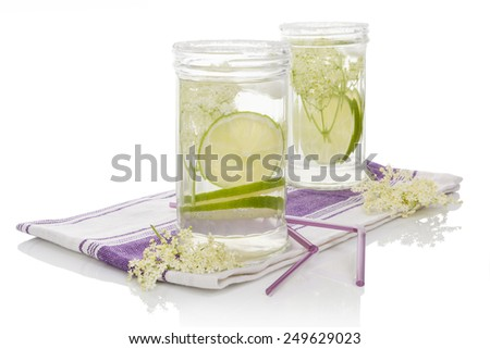 Elderberry lemonade. Two glasses with elderberry lemonade with ice and lime slices isolated on white background. - stock photo