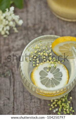 Elderflower and lemon juice on old wood table - stock photo