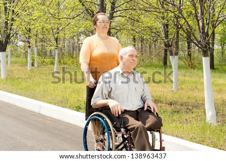 Elderly amputee with one leg amputated above the knee being taken for a walk in a wheelchair by his wife or carer - stock photo