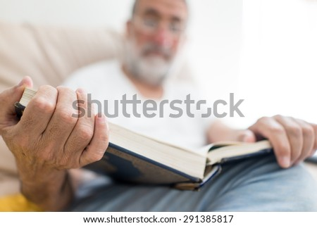 Elderly Arabic man sitting and reading book - stock photo
