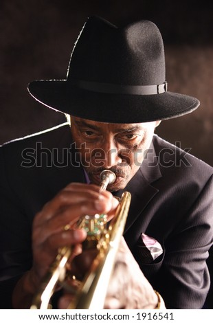 Elderly black man playing a trumpet. He has a soulful countenance. - stock photo