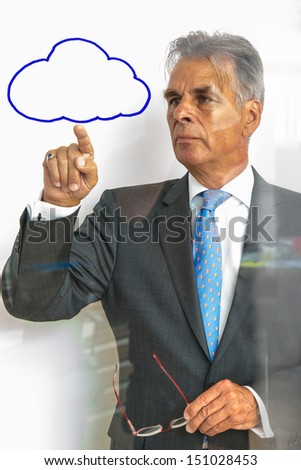 Elderly businessman pointing at a cloud being painted on glass with reflections. The cloud symbol can easily be removed, leaving space for your copytext on bright background - stock photo