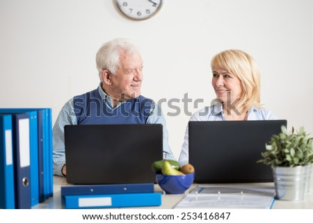 Elderly busy couple running together a business - stock photo