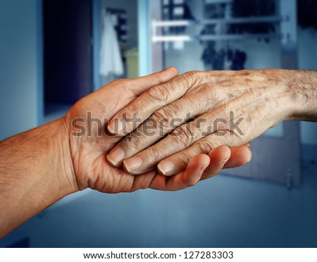 Elderly care and senior health services with the hand of a young person holding and helping an old and aging patient for in home medical help due to aging and memory loss in a hospital background. - stock photo