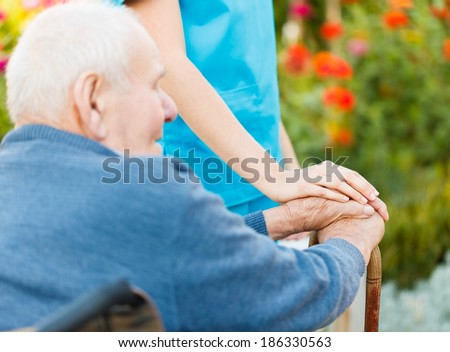 Elderly care in nursing home - doctor with patient. - stock photo
