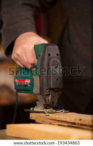 Elderly carpenter working in his workshop with handheld power tools smoothing and leveling the surface of a plank of wood as he pursues his hobby, close up of his hand - stock photo