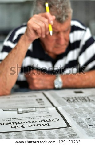 Elderly Caucasian Man Searching Classified Ads For Employment - stock photo