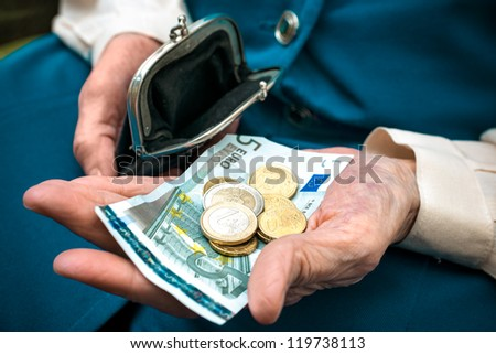 elderly caucasian woman counting money in her hands - stock photo
