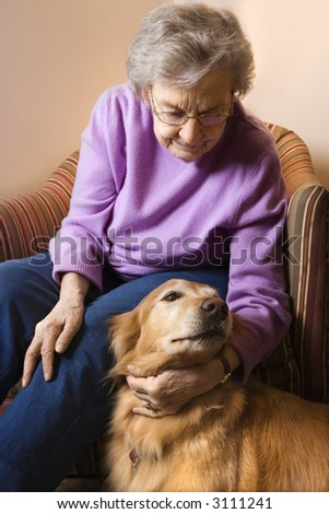Elderly Caucasian woman in bedroom at retirement community center petting therapy dog. - stock photo