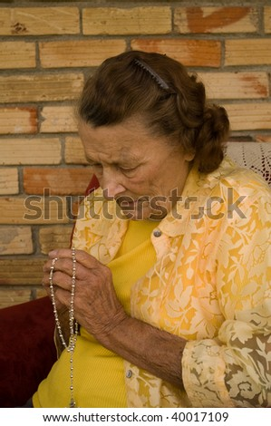 elderly caucasian woman with hands folded in prayer while holding a rosary - stock photo