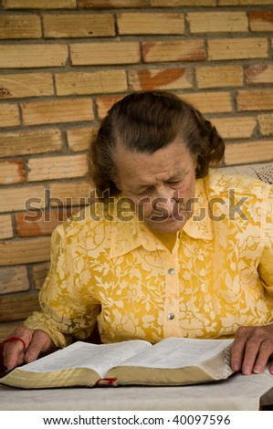 elderly caucasian woman with hands holding Bible as she reads studies the Word - stock photo