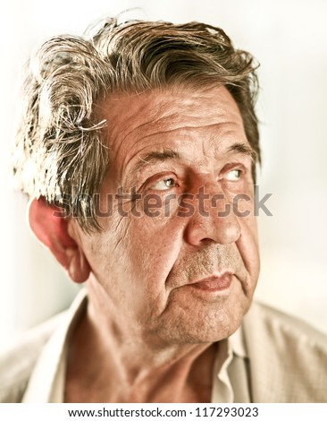 Elderly closeup sad man's face over white background - stock photo