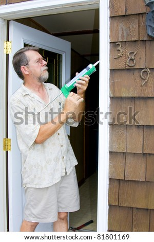 Elderly contractor caulking around glass door frame, sealing from possible air leaks, conserving energy - stock photo