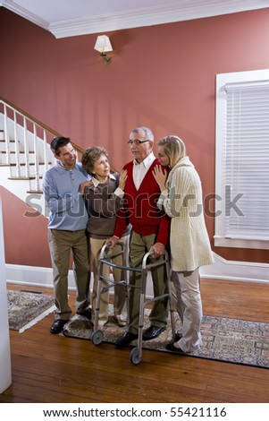 Elderly couple at home with adult children, senior man using walker - stock photo