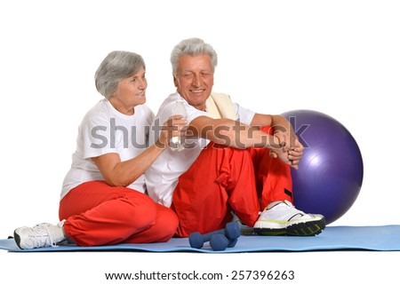 Elderly couple exercising,sitting on a floor of a gym isolated on white - stock photo