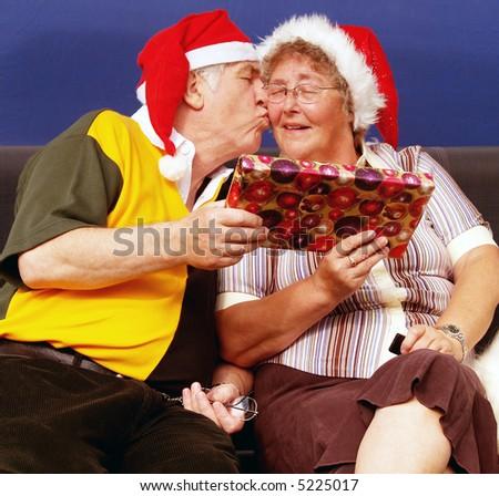 Elderly couple having a kiss at christmas - stock photo