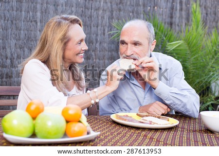Elderly couple having food on terrace - stock photo