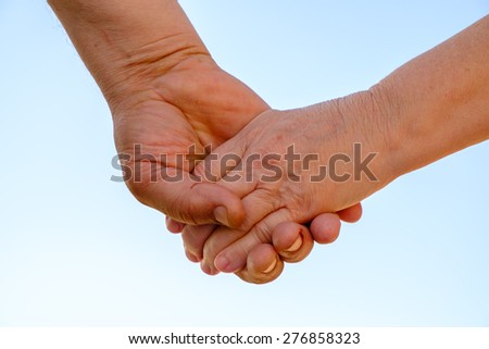 Elderly couple holding hands - stock photo
