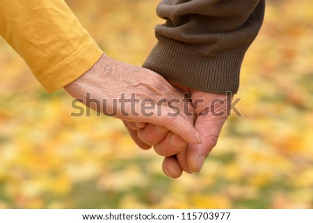 elderly couple holding hands in autumn park - stock photo