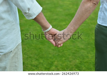 Elderly couple holding hands over green grass background - stock photo