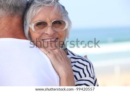 Elderly couple hugging on beach - stock photo