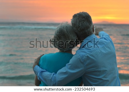 Elderly couple in love at sunset on a summer evening watching sea - stock photo