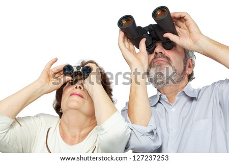 Elderly couple looks through binoculars - stock photo