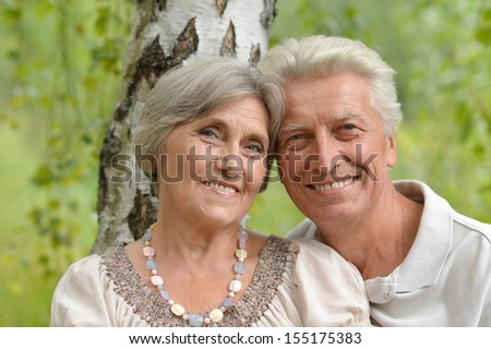 Elderly couple near the birch smiling looking into camera - stock photo