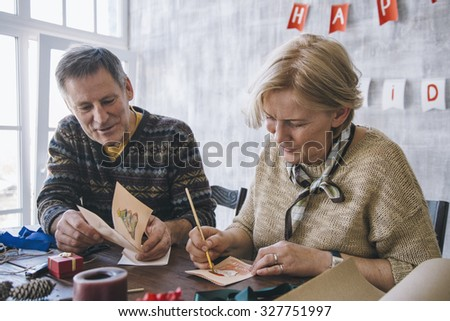 Elderly couple of blonde woman and brunet man painting Christmas cards together - stock photo