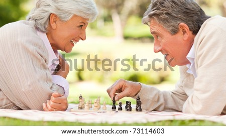 Elderly couple playing chess - stock photo