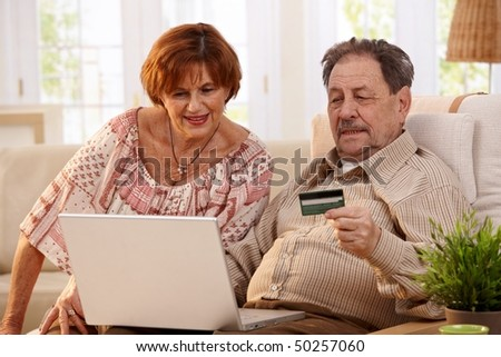 Elderly couple shopping online at home, using laptop computer and credit card. - stock photo