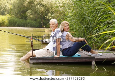 Elderly couple sit back to back each other on the pier. Happy senior people relaxing at the lakeside while they fishing.  - stock photo